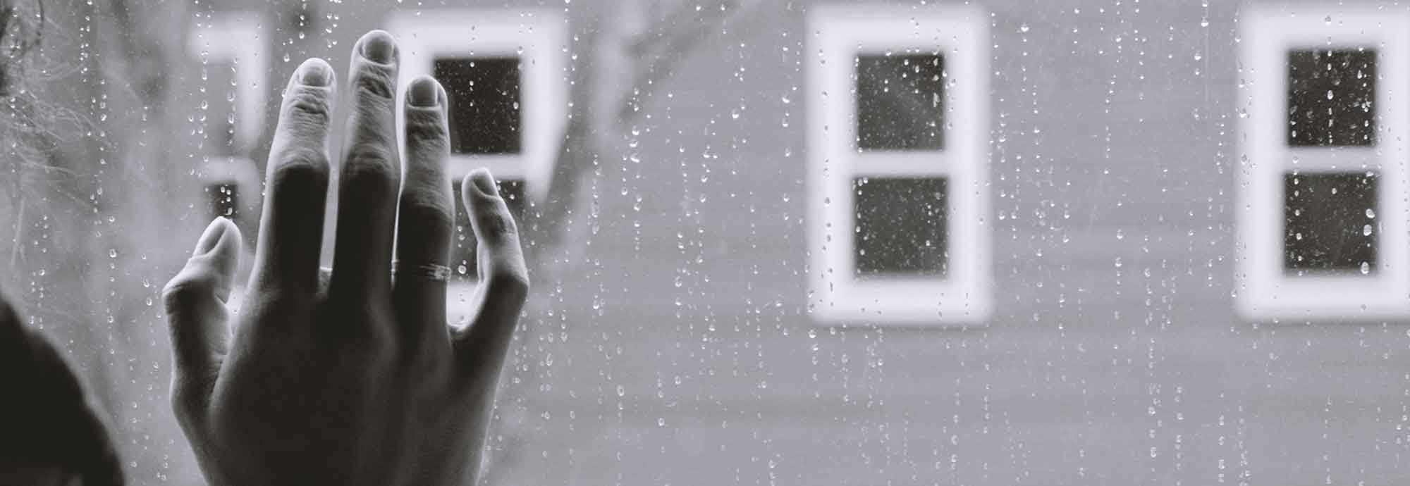 someone's hand placed on a rainy window, looking out at other windows